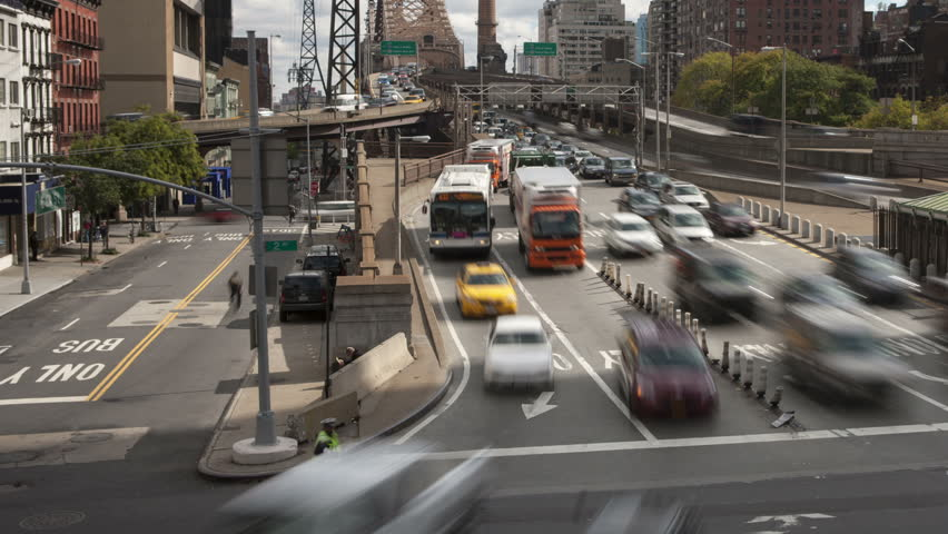 NEW YORK - OCTOBER 18: (Time-lapse) Mid-day traffic enters Manhattan from Queens on the Queensboro Bridge as the Roosevelt Island Tram leaves the station on October 18, 2012 in New York, NY