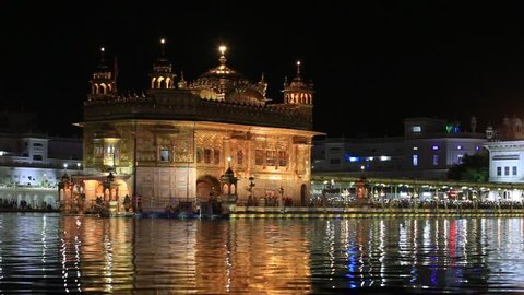 AMRITSAR, INDIA - SEPTEMBER 28, 2014: Unidentified sikhs and indian people visiting the Golden Temple in Amritsar at night. Sikh pilgrims travel from all over India to pray at this holy site.