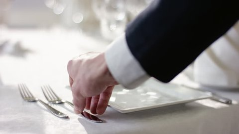 Shot of waiter hand preparing dinner table for celebration at banquet hall