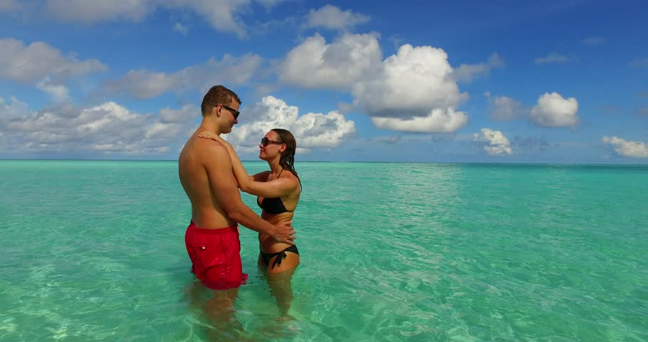 v15498 two 2 people together having fun man and woman together a romantic young couple sunbathing on a tropical island of white sand beach and blue sky and sea
