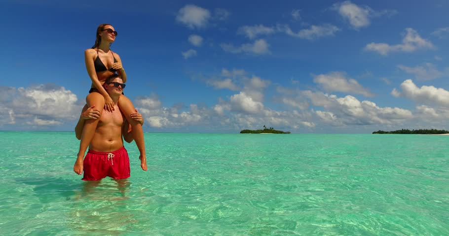 v15466 two 2 people together having fun man and woman together a romantic young couple sunbathing on a tropical island of white sand beach and blue sky and sea