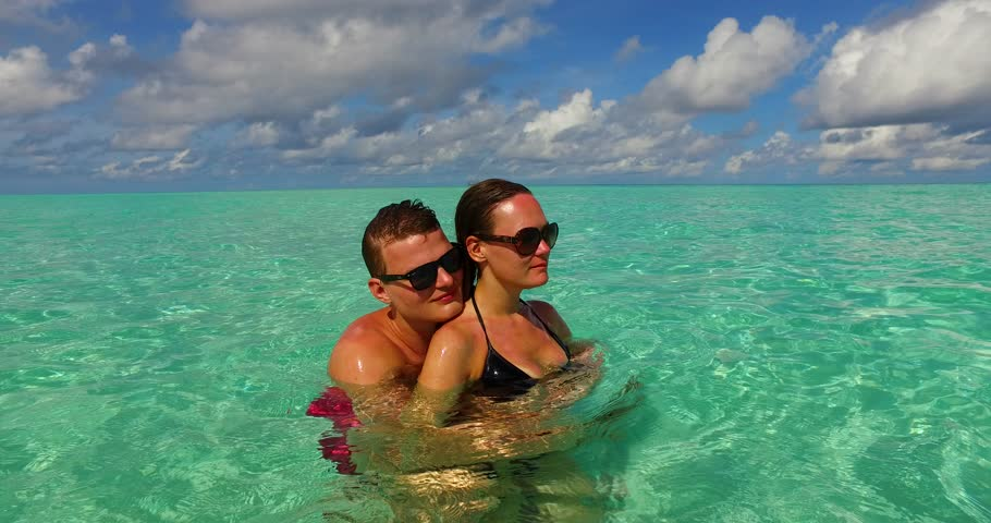 v15512 two 2 people together having fun man and woman together a romantic young couple sunbathing on a tropical island of white sand beach and blue sky and sea