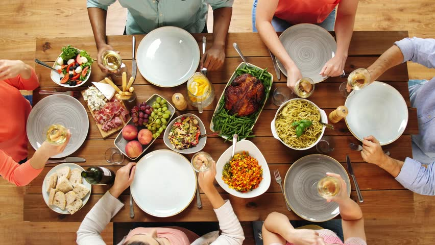 Eating and holidays concept - group of people at table with food clinking wine glasses