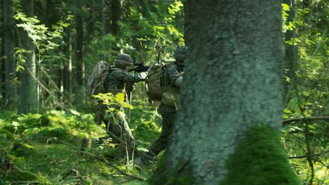 Squad of Five Fully Equipped Soldiers in Camouflage on a Reconnaissance Military Mission, Rifles in Firing Position. They're Running in Formation Through Dense Forest. Side View Long Shot.