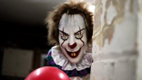 Evil Clown in Dark Scary Halloween Horror Scene, Frightening with Balloon
