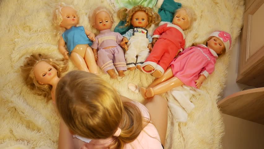Pretty girl plays with a doll at home. Doll listening. Play one at home.