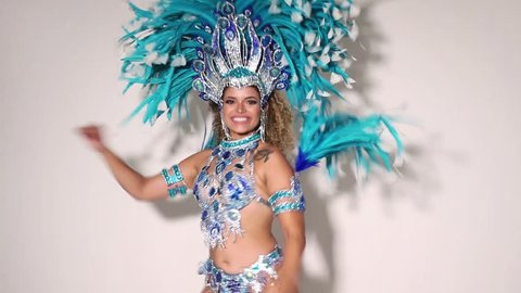 Beautiful and happy brazilian woman dancing samba while wearing traditional costume