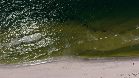 waves are gently washing up the beach sand, aerial view
