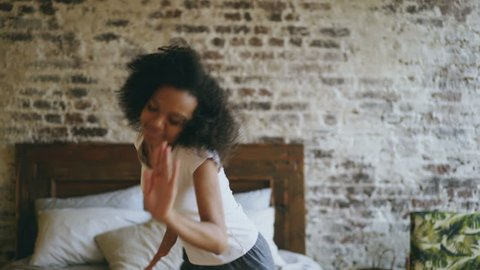 Attractive mixed race young joyful woman have fun dancing near bed at modern apartment