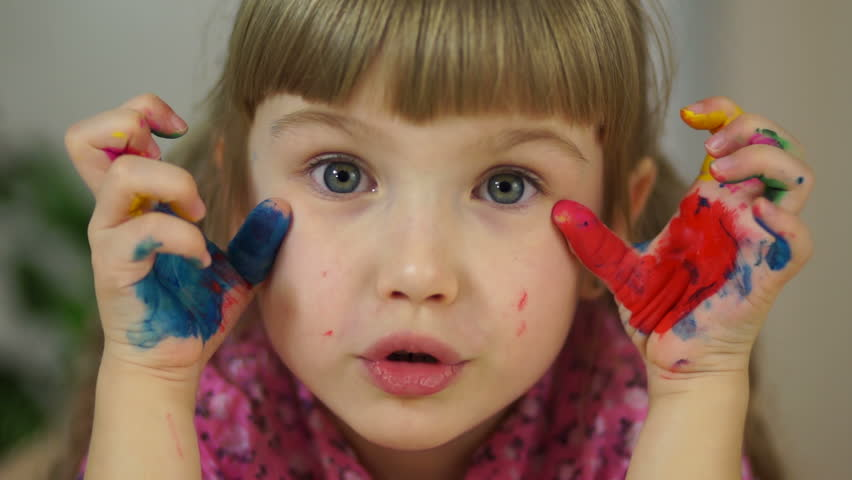Close-up portrait of a girl. Girl hamming at camera. Girl covered in paint