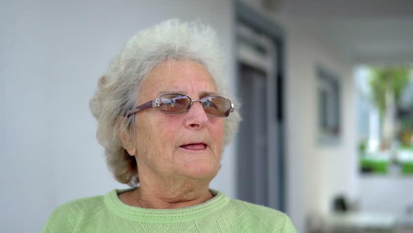 Portrait of elderly white sad woman sitting and thinking outdoors