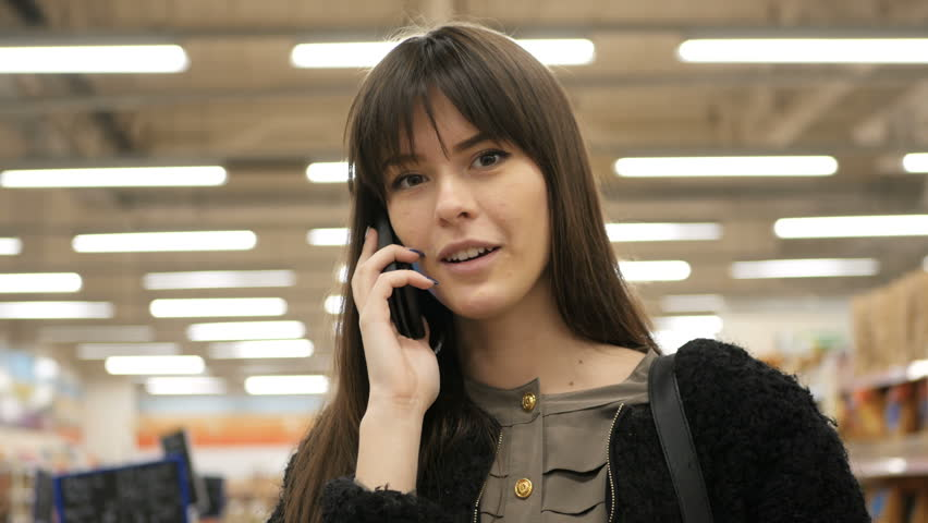 Smiling woman doing grocery shopping at the supermarket and having a phone call with her smartphone | Shutterstock HD Video #32724385