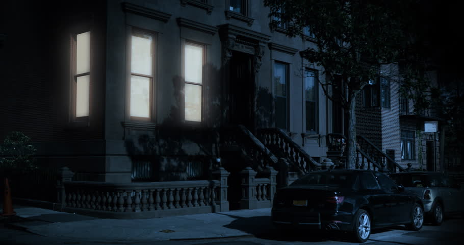 A nighttime exterior establishing shot of the first floor of a typical Brooklyn brownstone residential home as a room's windows lights up then turns off.