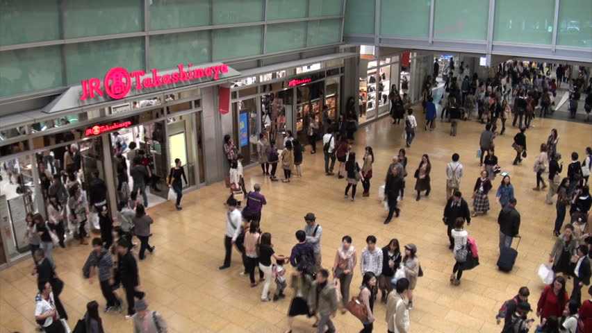 NAGOYA, JAPAN - 20 OCTOBER 2012: Commuters walking through the busy Nagoya train station during rush hour (handheld video from escalators, includes zoom towards main transit hall)