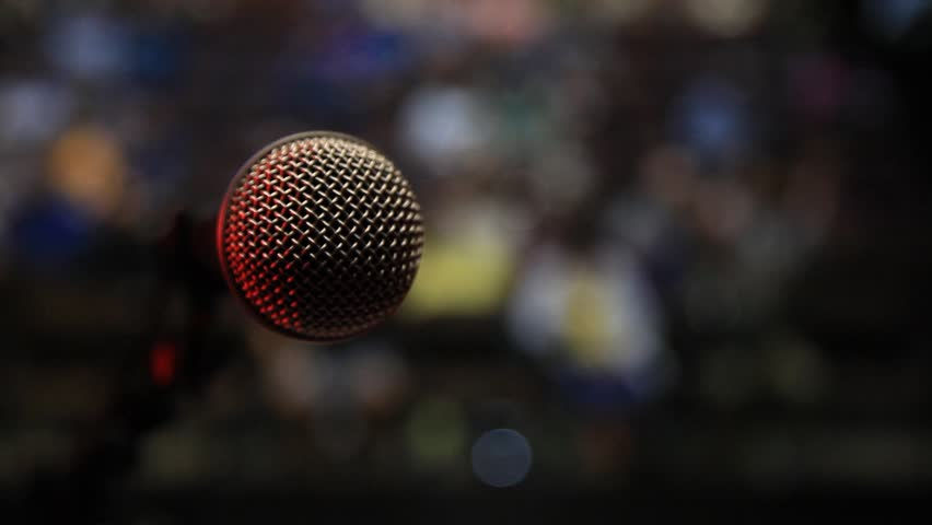 Point of view of a singer stepping up to microphone before a live audience