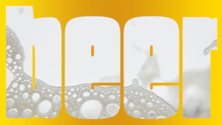 Pouring beer in a transparent glass, creating a thin layer of white foam, and completing the letter pattern B-E-E-R. Yellow color on black background. Macro close-up shot.