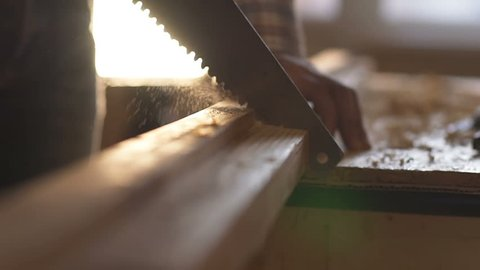 A man sawing wood Board with hand saw. Macro. Slow motion