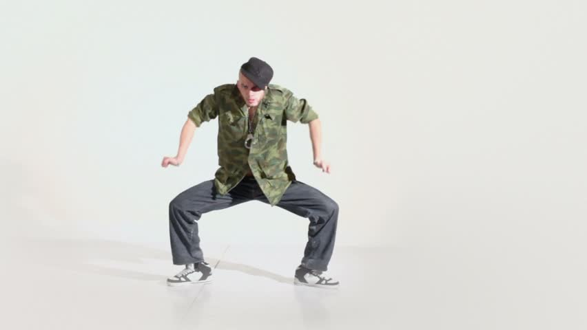Hip-hop dancer in cap dances lit by light in photo studio with white background