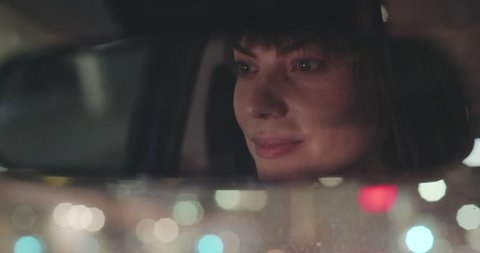 Cinematic shot of a happy woman driving at night.