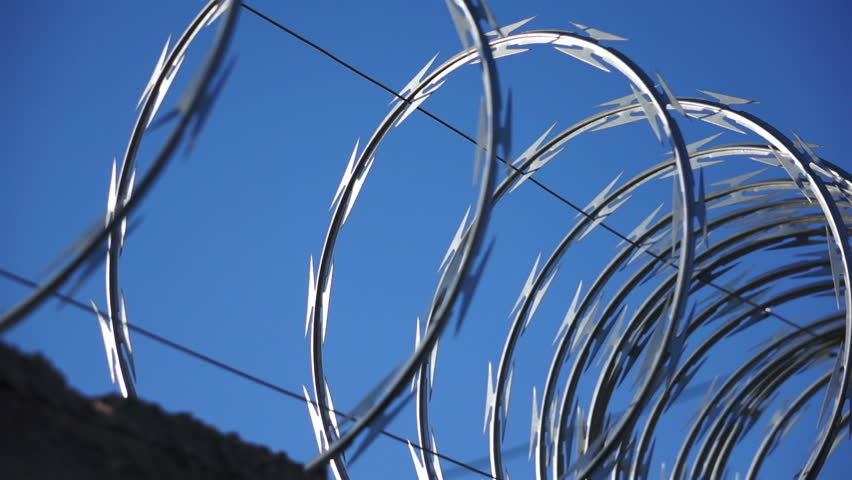 A close up, dolly shot of razor wire glistening in the sun against a blue sky.