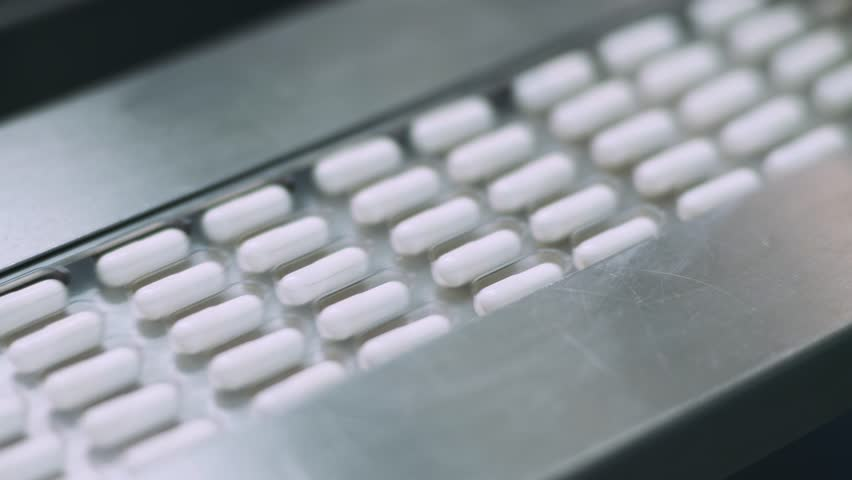 Production of pharmaceuticals and drugs, large number of capsules, white tablets on the conveyor, production line.