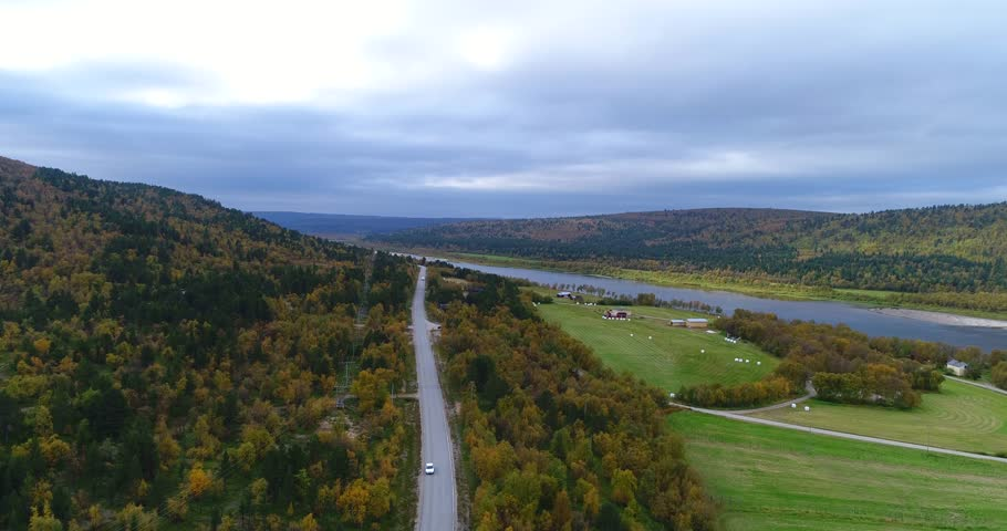 Autumn color landscape, Cinema 4k aerial pan view of mountains and fields, full of different colors, near tenojoki river, on a cloudy day, in Lapland, Finland