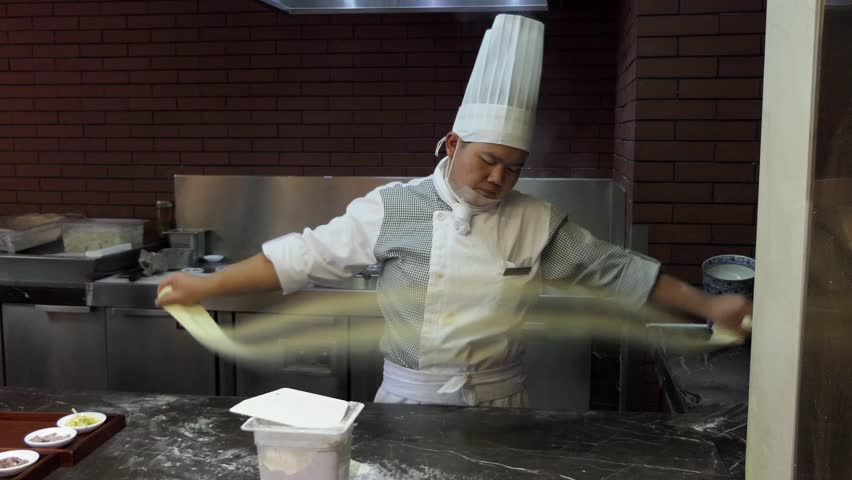 LANZHOU, CHINA - JULY 2017 - Asian restaurant kitchen with Chinese chef cooking food, man as professional cook working in hotel, preparing traditional noodles with dough. Lanzhou, China, Asia