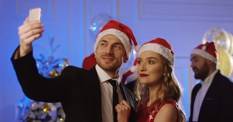 Young attractive couple making nice selfies in the Santa Claus hats at the glamourous Christmas party. Inside