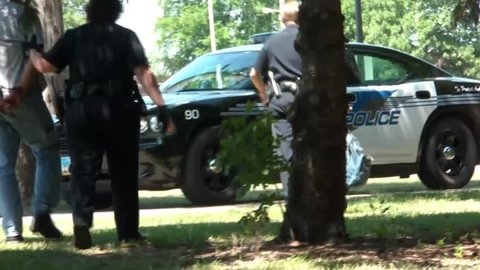 Man appearing to be homeless by a river is arrested by police and then promptly taken to a cruiser.