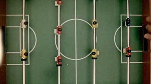 Fake 8mm amateur film: playing table-soccer. Shot from above.