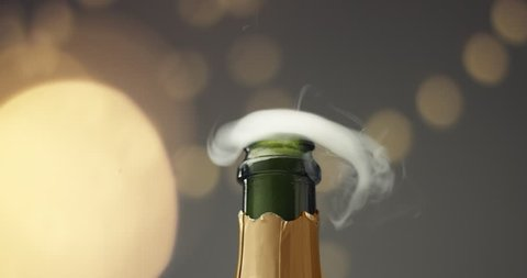 Close up slowmotion video of man's hands opening a bottle of champagne on gray background with lights and flares