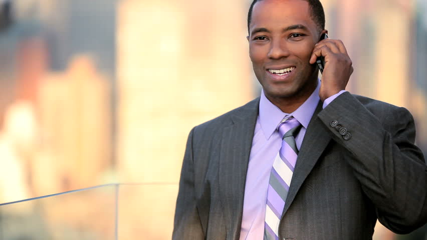 African American male business manager on a cell phone on rooftop overlooking NYC