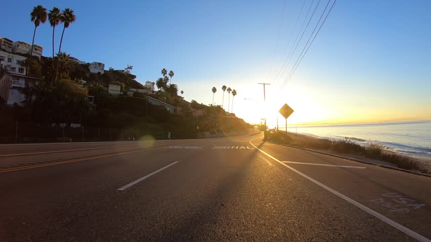 Los Angeles, California, USA - November 18, 2017:  Slow motion driving into sunrise on Pacific Coast Highway between Malibu and Santa Monica.