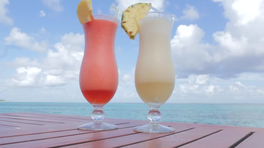 Tropical winter vacation with Pina Colada cocktail and passion fruit drink on the table with Indian ocean view. Ocean view with tropical cocktails. Close up of two glasses with cold refreshing drink.