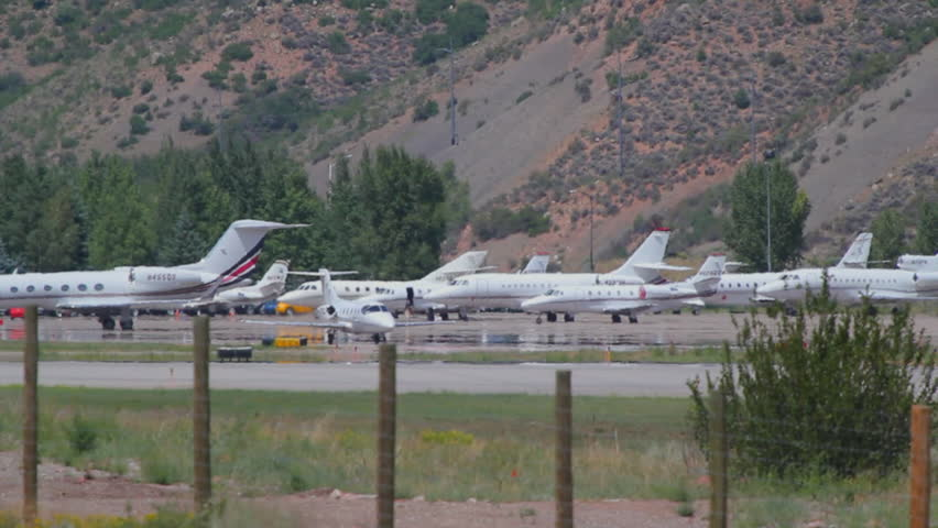 Aspen, CO - July, 2012: Learjet 31A taxis down runway to takeoff point and flies away