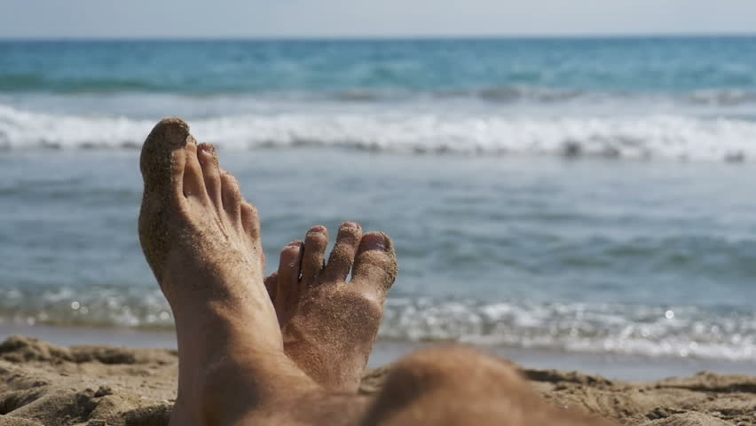 Legs of Men Lying on Beach near the Sea, POV. Slow Motion in 96 fps. Man lie on the sandy beach, overlooking the Sea. Young man relaxing on a resort. | Shutterstock HD Video #32936890