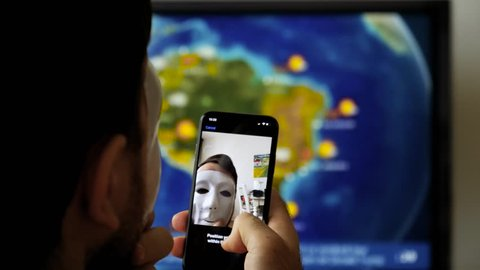 PARIS, FRANCE - CIRCA 2017: Face Obstructed message on display of new Apple iPhone X with Face ID virtual facial recognition function anonymous hacker wearing a mask - data monitor in the background