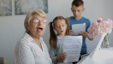 Grandmother with grandchildren playing piano and singing songs.