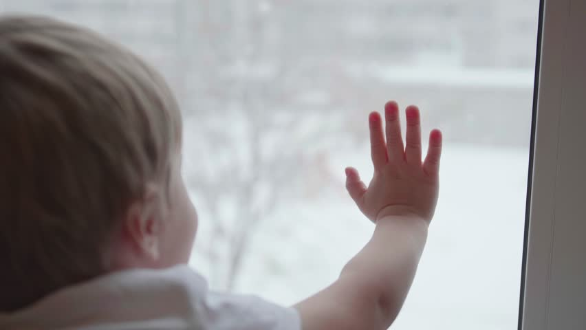 A child stands near a window and watching snow falling on the street. The closeup hand on the glass window | Shutterstock HD Video #32941210