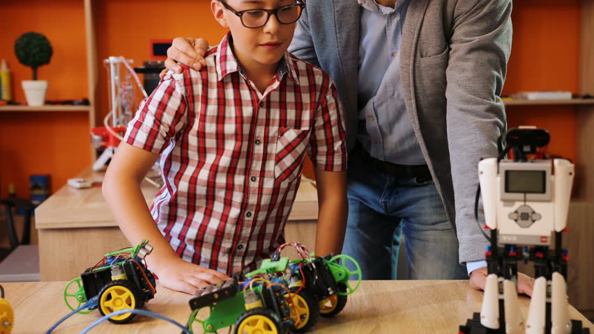 Portrait of male teacher with his boy pupil in the glasses posing to the camera with their mastered robot in the modern classroom | Shutterstock HD Video #32941240