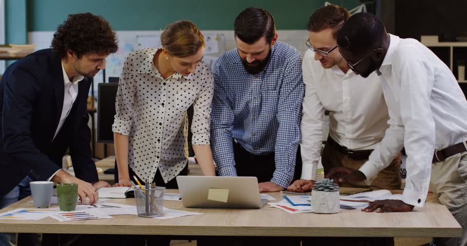 Multy ethnical office workers team leaning on a conference table with documents, charts, graphics, laptop and financial reports on it while creating business plans. Inside of modern cozy office | Shutterstock HD Video #32941660