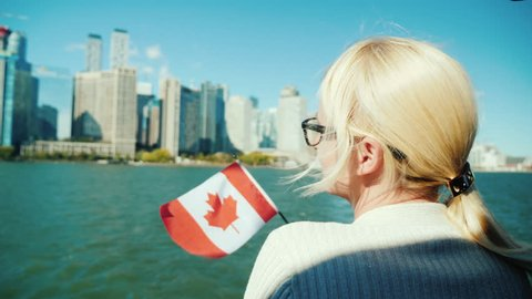 A woman with the canada flag looks at Toronto cityscape from the ship. Tourism in Canada concept
