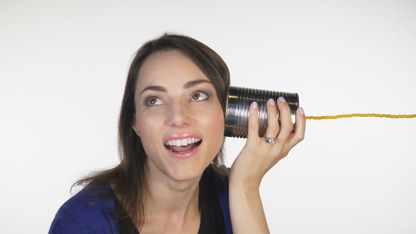 Attractive woman has conversation on tin can telephone. Obsolete technology.