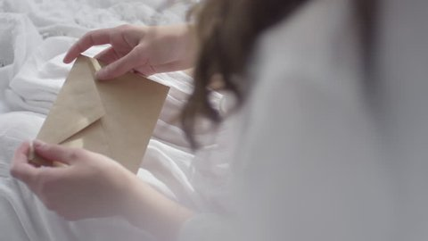 Top view of unrecognizable woman with long hair sitting in bed on early morning and opening envelope with letter from lover