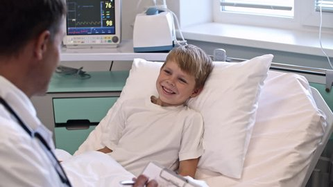 Little cute boy lying on hospital bed and smiling while listening to male doctor writing on clipboard