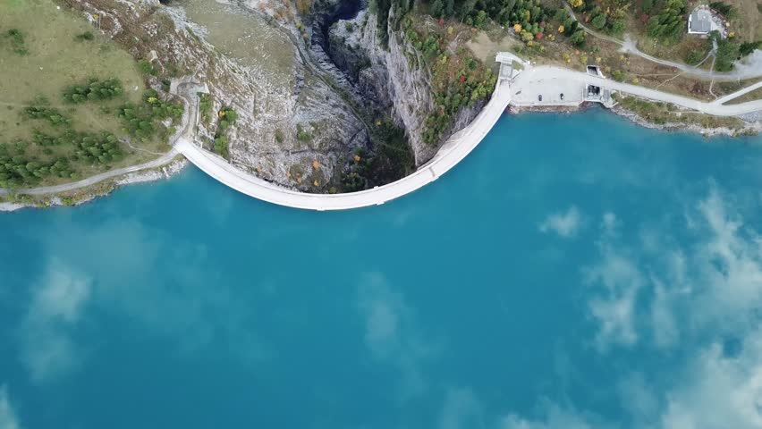Drone aerial footage of reservoir lake and arch dam for renewable energy power plant in Switzerland Alps, top down view. 4K video