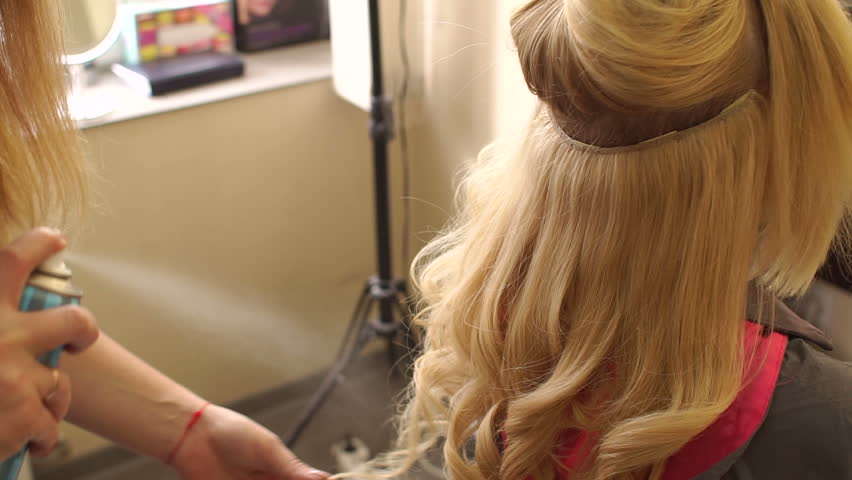 Close-up of hairdresser's hands using hairspray on client's hair at salon. Hairdresser spray hair spray on the girl's hair, close-up.