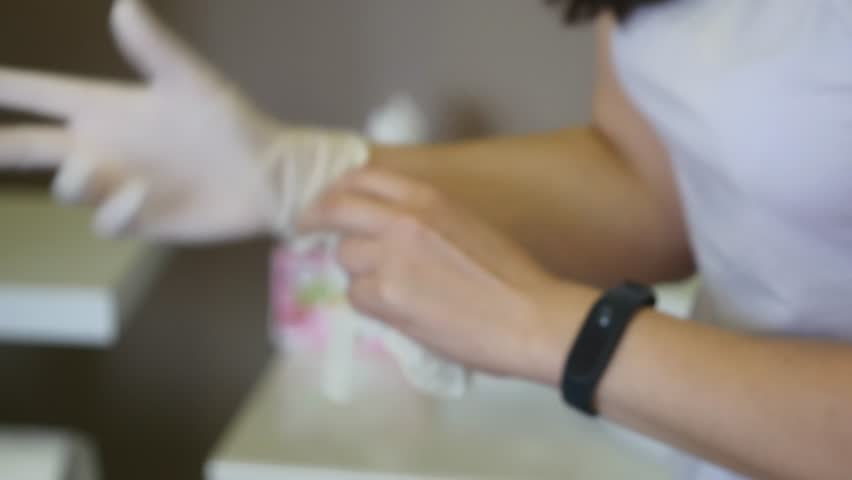 Beautician putting on rubber glove on her hand | Shutterstock HD Video #33004360