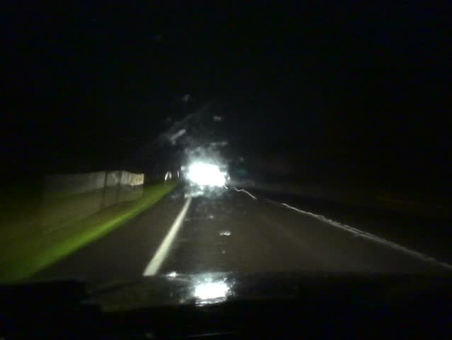 Time lapse footage of driving at night on a dark country road, passing through small villages.