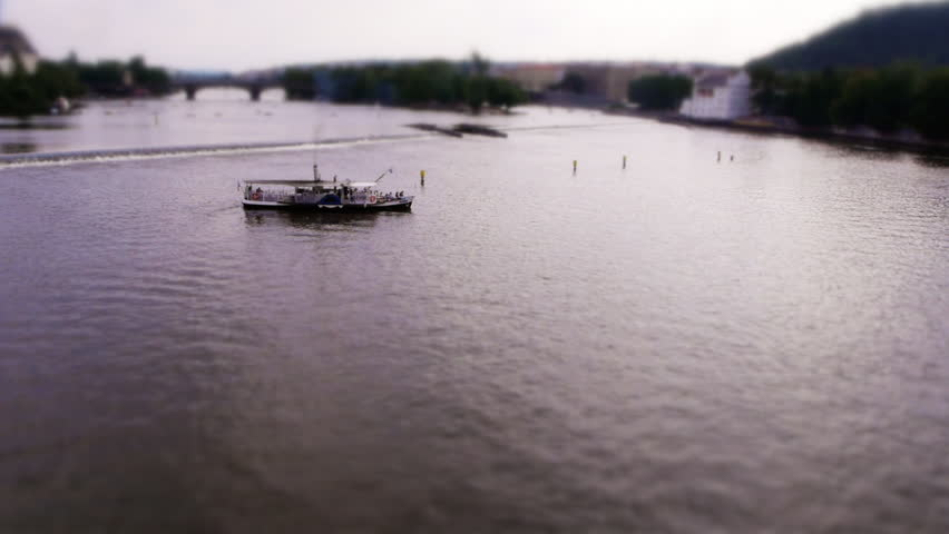 Miniature Boat turning around on Vltava river at the Charles Bridge in Prague (Tilt-shift)